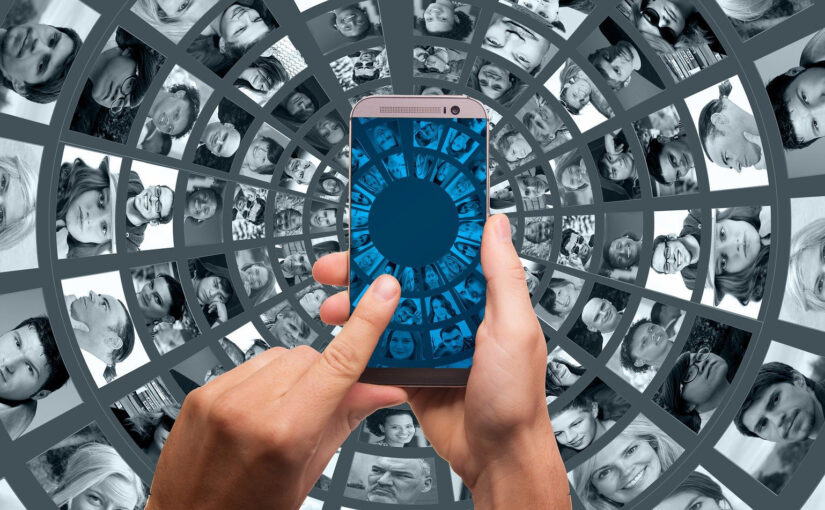 Finger on mobile phone background vortex of screens showing peoples faces