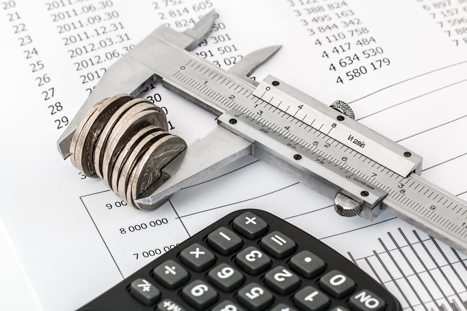 bank statement, calculator and small pile of coins being measured