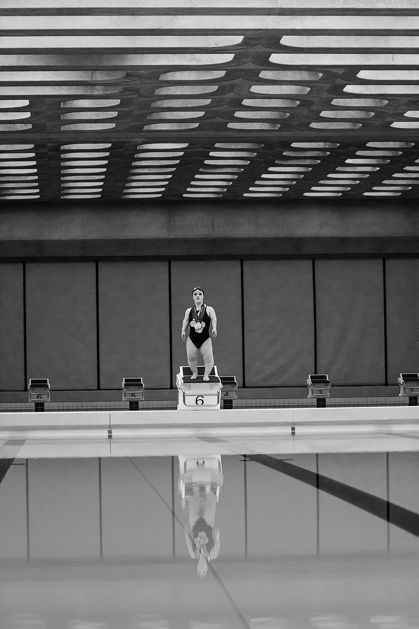 Black and white image of paralympic swimmer Ellie Simmonds standing on diving board