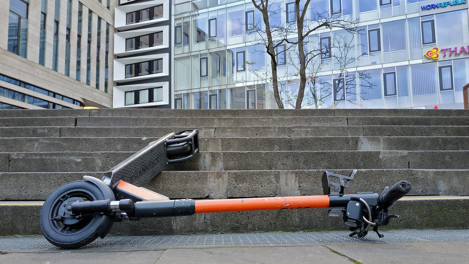 an abandoned e-scooter lying on its side at the foot of outdoor steps