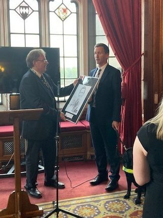 Lord Chris Holmes standing with guide dog Nancy in front of ornate stained glass windows to receive his IPT fellowship cartoon gift - being presented by John Howells MP